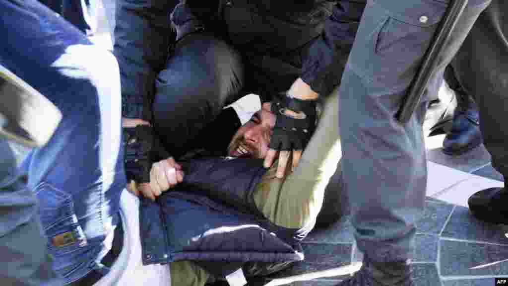 Azerbaijani police officers detain an opposition activist during an unauthorized rally in central Baku to demand the resignation of President Ilham Aliyev. (AFP/Tofik Babayev)