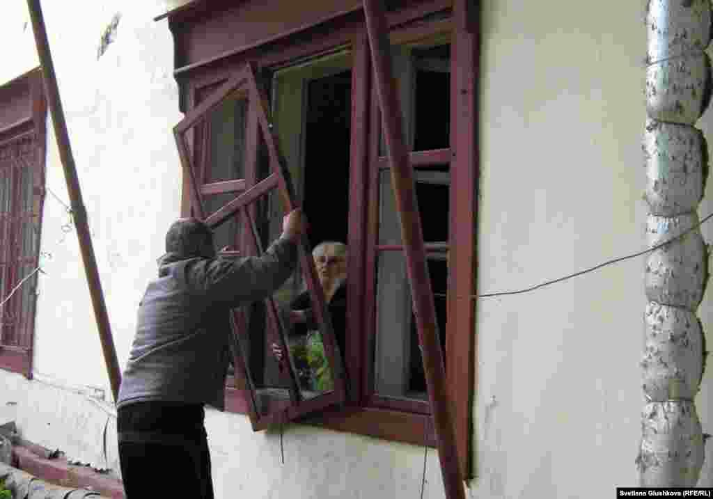 Жильцы пытаются вставить оконную раму, которую вынесло ударом взрывной волны. Астана, 24 мая 2011 года. - Жильцы дома пытаются вставить оконную раму, которую вынесло ударом взрывной волны. Астана, 24 мая 2011 года