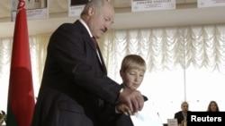 Беларус Президенти А.Лукашенка ўғли Николай билан Минскдаги сайлов участкасида овоз бермоқда, 2012 йил 23 сентябр.