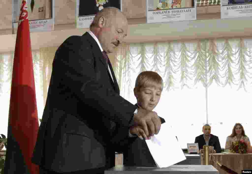 Belarusian President Alyaksandr Lukashenka, accompanied by his son Mykalay, casts his ballot at a polling station in Minsk.