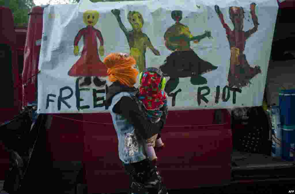 "A mother holding her baby walks past a car with a banner reading ""Free Pussy Riot"" during a demonstration supporting the Russian performance artists Pussy Riot in Prague. (AFP/Michal Cizek)"