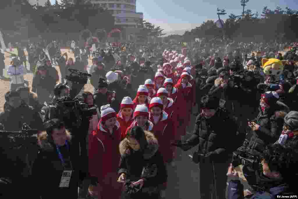 "North Korean cheerleaders are surrounded by media as they attempt to walk on Gyeongpo Beach in Gangneung, South Korea. The North's 229-strong cheering squad, dubbed the ""Army of Beauties,"" have drawn a lot of attention since arriving for the Pyeongchang Winter Olympics last week. (AFP/Ed Jones)"