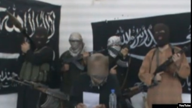 Jund al-Khilafah (Soldiers of the Caliphate), a previously unknown group, reads a statement threatening the Kazakh government.