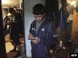 Тәжік мигранты телефонымен хабарлама жіберіп тұр. Мәскеу, 23 қыркүйек 2009 жыл.