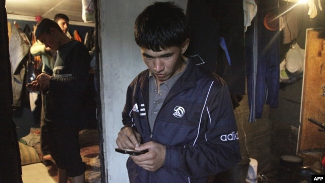 Young Tajik migrant workers send text messages from their shared residence in the Russian capital, Moscow. (file photo)