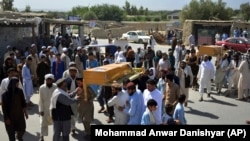 FILE: Men carry the coffin of a relative who died during Afghan forces' raid on a house in Chaparhar district of Nangarhar province in May.