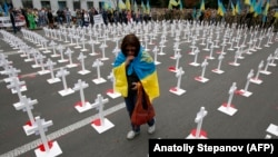 A grieving woman wears the Ukrainian flag as she walks among white crosses with portraits of dead Ukrainian soldiers in front of the Russian Embassy in Kyiv in August.