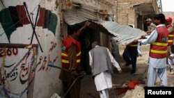 Police officers and rescue workers are seen at the entrance of damaged election campaign offices belonging to the Pakistan Peoples Party (PPP) after a bomb blast in Quetta on May 10.