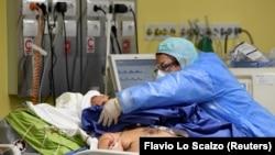 Un cadru medical îngrijind un pacient bolnav de COVID-19 la secția de terapie intensivă a unui spital din Milano, Italia