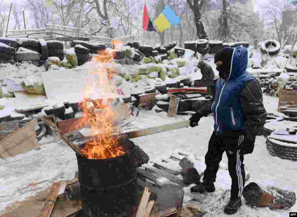 A protester warms himself near a fire at a barricade close to the regional administration building in Lviv.