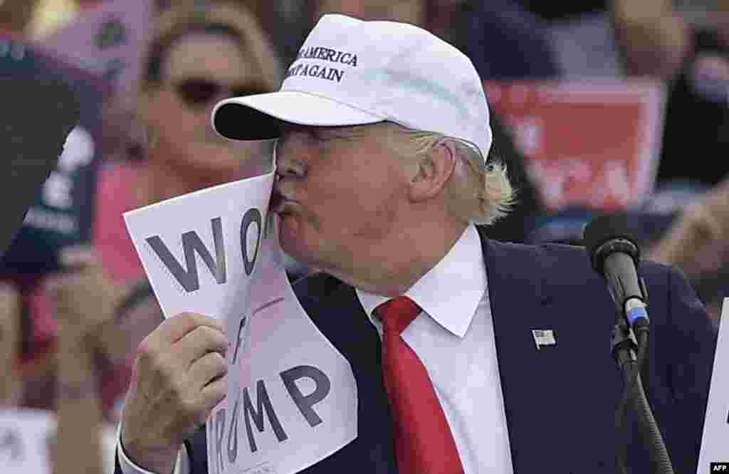 "U.S. Republican presidential candidate Donald Trump kisses a ""Women for Trump"" placard during a rally in Florida on October 12. (AFP-Mandel)"