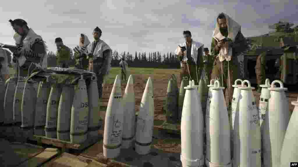 Israeli soldiers perform morning prayers next to artillery shells at an Israeli Army deployment area near the Israel-Gaza Strip border. (AFP/Menahem Kahana)