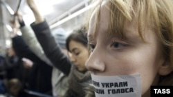 "A woman takes part in a flash mob in the Moscow subway, with a sticker on her mouth saying, ""They stole our voices."" (ITAR-TASS/Aleksandr Sorin)"