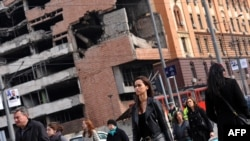 Serbia -- Pedestrians cross a street in Belgrade near the former federal military headquarters destroyed during the 1999 NATO air campaign against Yugoslavia, March 10, 2014. Photo by Andrej Isakovic (AFP).