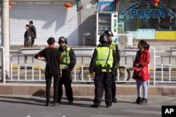 Шыңжаң-Ұйғыр автономиялық өлкесінде полицейлер жергілікті тұрғындарды тексеріп тұр. Қараша айы 2017 жыл