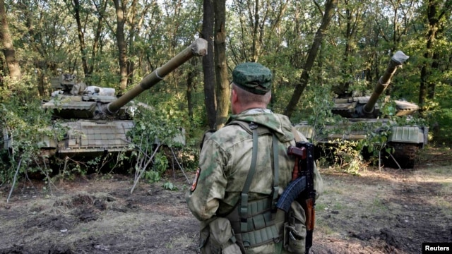 A pro-Russian separatist from the Vostok Battalion stands in front of T-64 tanks in Donetsk on July 16.