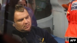 Ukrainian opposition activist Dmitry Bulatov sits in an ambulance at the airport in Vilnius, where he arrived for treatment on February 2.
