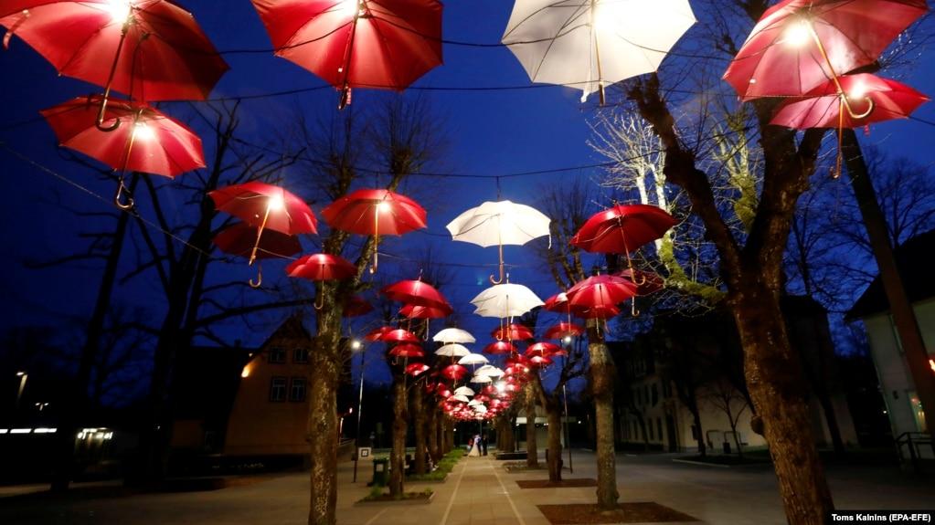 Почти безлюдная свадьба в период пандемии – под инсталляцией из зонтиков в цветах национального флага. Огре, Латвия, 5 мая 2020 года