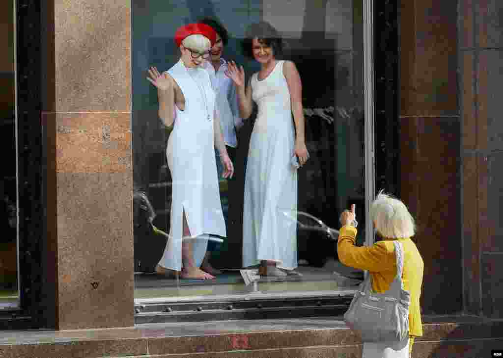 A woman gives a thumbs up to women posing in a shop window of a shopping mall in downtown Kyiv. (epa/Serhiy Dolzhenko)