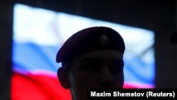 RUSSIA -- A serviceman stands in front of a screen displaying a Russian flag during a news briefing, organized by Russian defence and foreign ministries and dedicated to SSC-8/9M729 cruise missile system, at Patriot Expocentre near Moscow, Russia January