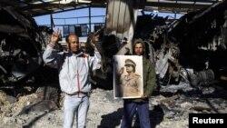 Сторонники Каддафи на месте разбомбленного склада военной техники в Триполи, 22 марта 2011