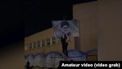 Али Хаменеинин сүрөтүн айрып жаткандар.