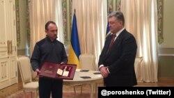 Ukrainian President Petro Poroshenko (left) presents a Hero of Ukraine award for Reshat Ametov to his brother in March 2018.
