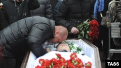 Mikhail Markelov, the brother of slain human rights lawyer Stanislav Markelov, pays his last respects at his brother's funeral in Moscow in 2009.