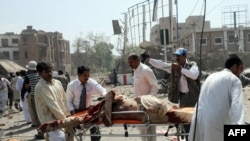 Volunteers transport an injured victim at the scene of the suicide car bomb attack in Lahore on May 27.