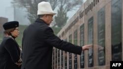 Президент Атамбаев инқилоб қурбонлари хотирасига ўрнатилган ëдгорлик ëнида.