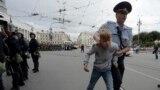 Un polițist escortează un adolescent care a participat la un protest în St. Petersburg, 9 septembrie 2018
