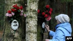 A woman cleans a plaque for a victim of Stalin's purges at a memorial on the outskirts of St. Petersburg.