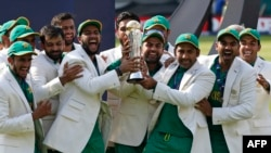 FILE: Pakistan's Sarfraz Ahmed (3rd R) holds the trophy as Pakistan players celebrate their win at the presentation after the ICC Champions Trophy final cricket match against India at The Oval in London in June.