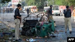 Police officials stand beside a mangled auto-rickshaw at the site of a suicide bomb attack in Peshawar.