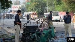 Police officials stand beside a mangled auto-rickshaw at the site of a suicide bomb attack in Peshawar, September 23, 2014.