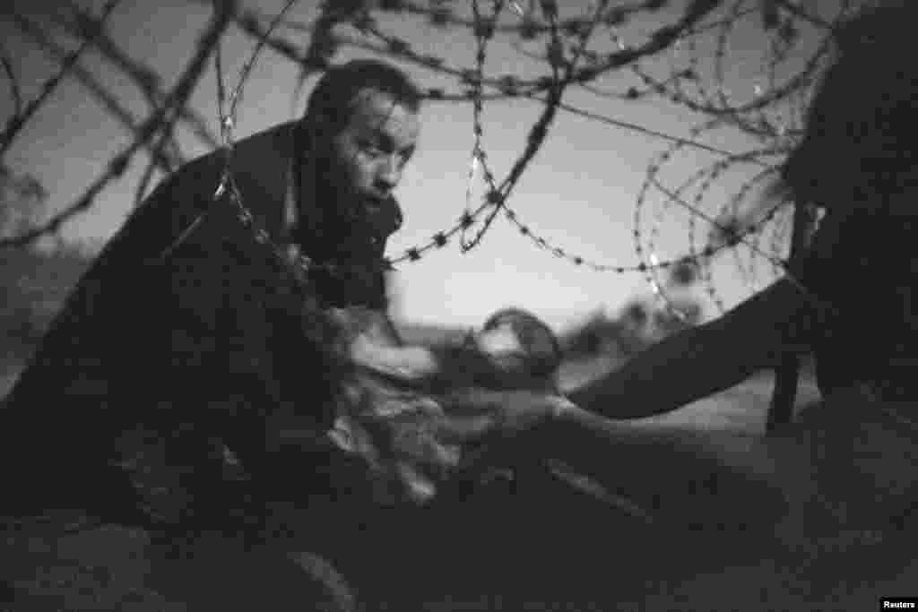 """Fotografia e vitit 2015, e Shtypit Botëror, dhe çmimi i parë për """"lajmin ekzkluziv nga vendi i ngjarjes"""" u fitua nga fotografi i pavarur, Warren Richardson, për këtë imazh. Fotografia, e cila u shkrep pothuajse në errësirë, tregon një migrant duke e kaluar një foshnje nën telat gjemborë të gardhit, në kufirin Serbi-Hungari, në Roszke. (28 gusht 2015)"""