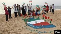 کودکان جزیره ابوموسی در حال شادی در اطراف پرچم ایران بر روی شنهای ساحل خلیج فارس