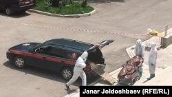 Медики в защитных костюмах загружают тело умершего от коронавируса человека в специальную машину. Июль 2020 года.