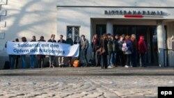 Луѓе држат транспарент за солидарност со жртвите од Аушвиц пред објектот каде се одвива судењето на Гроенинг.