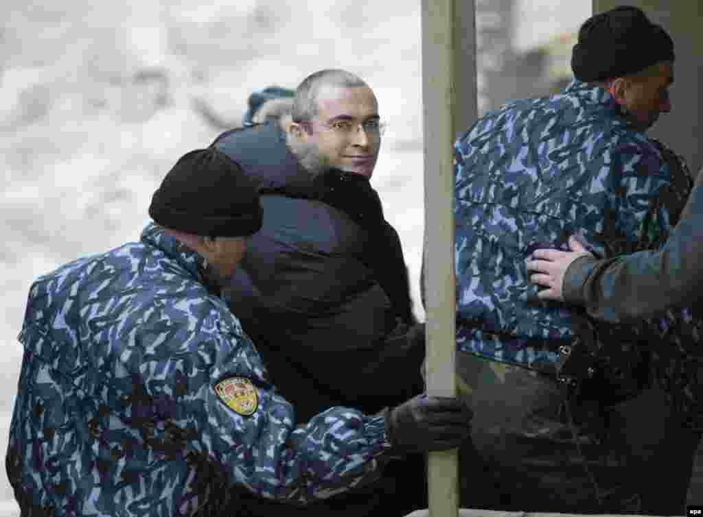 Russian police escort the former Yukos oil chief to a courthouse in Moscow on December 23, 2003.