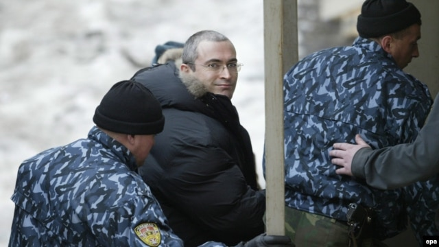 Former Yukos head Mikhail Khodorkovsky (center) is escorted into a court in Moscow in December 2003, less than two months after his arrest, for a hearing on prolonging his pretrial custody.