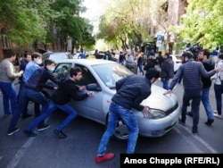 Protesters in Yerevan push a taxi after it tried to move through the crowd.