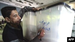 """An electoral worker writes """"rejected"""" on a ballot box in Baghdad in February 2009."""