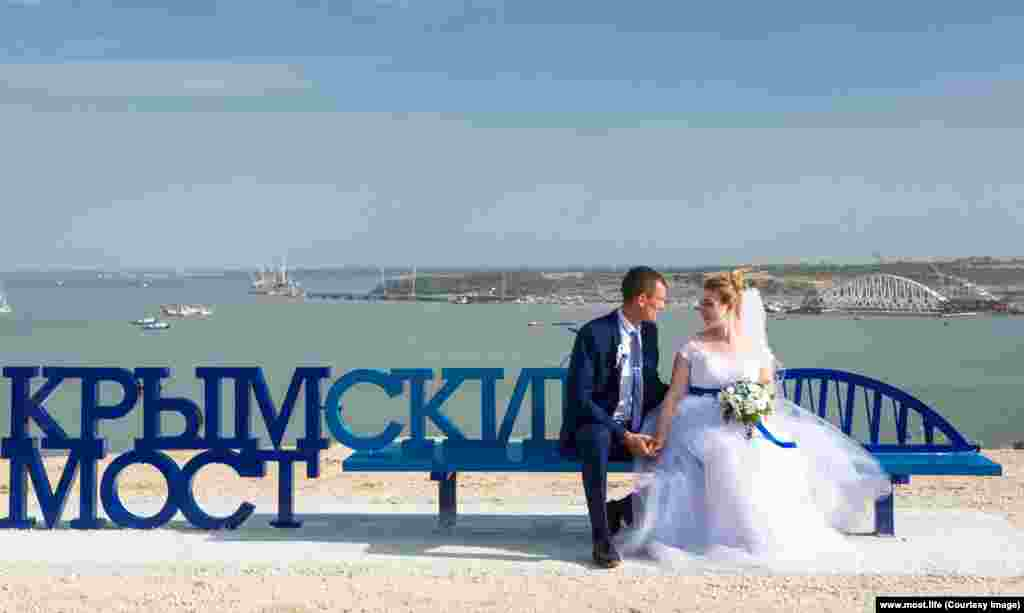 Newlyweds perch on a freshly installed bench overlooking the Crimean end of the bridge.