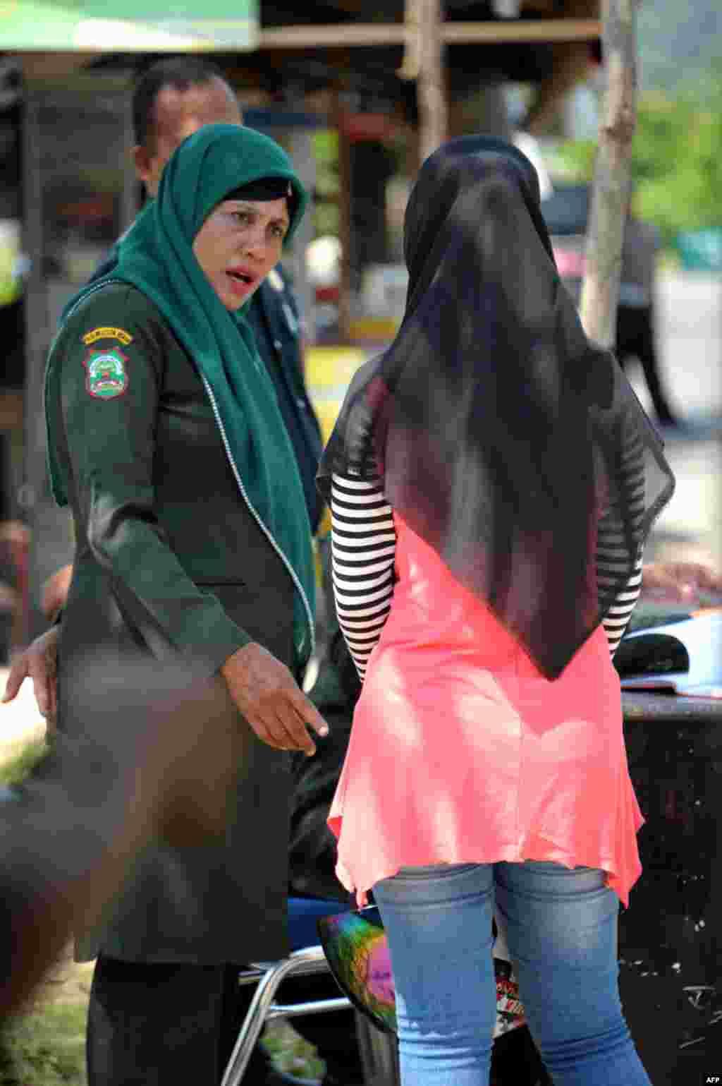 پلیس شریعت در حال تذکر دادن به یک زن اندونزیایی به خاطر پوشیدن شلوار جین تنگ