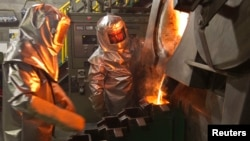 Workers pour molten gold from a crucible into moulds in a workshop at Kyrgyzstan's Kumtor gold mine. (file photo)