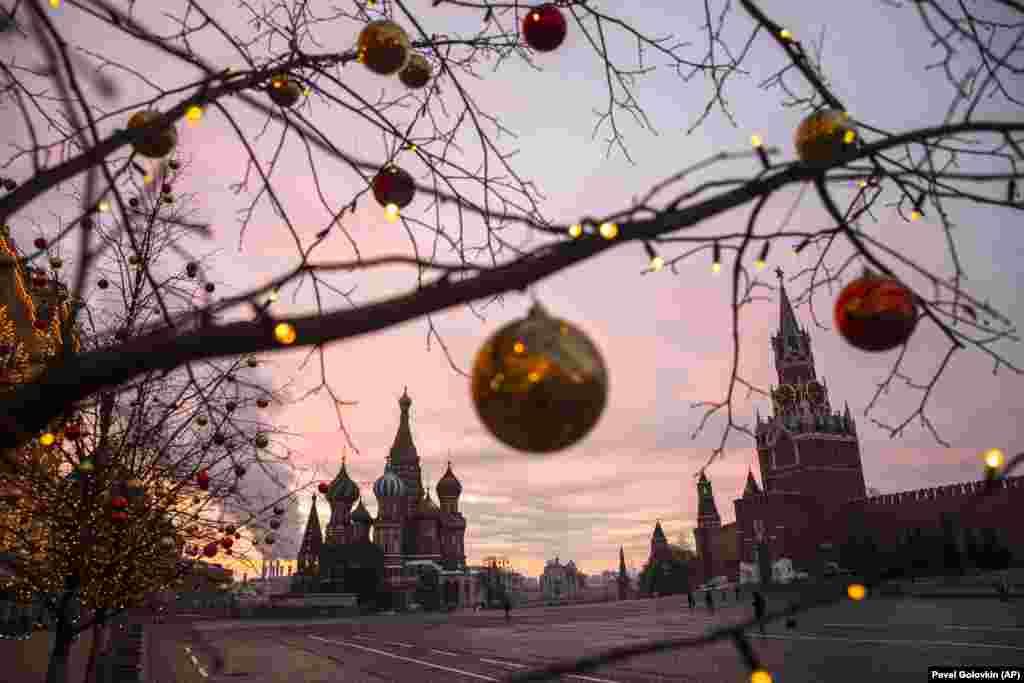 Лампиони и светла се гледаат на дрвјата украсени за Божиќ и Нова Година за време на изгрејсонцето над Црвениот плоштад, со катедралата Свети Василиј и кулата Спаскаја, десно, во позадина во Москва, на 12 декември 2020 година. Московскиот градоначалник Собјанин рече дека нема да има масовни новогодишни прослави во градот оваа година поради постојаната пандемија.