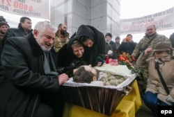 Relatives and friends react during the funeral ceremony in Kyiv for Ukrainian soldier Leonid Dergach, who was killed in renewed fighting near Avdiyivka in eastern Ukraine in early February.