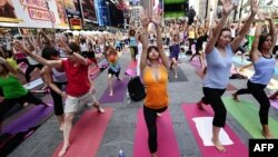 Participanţi la o sesiune practică yoga, Times Square, New York.