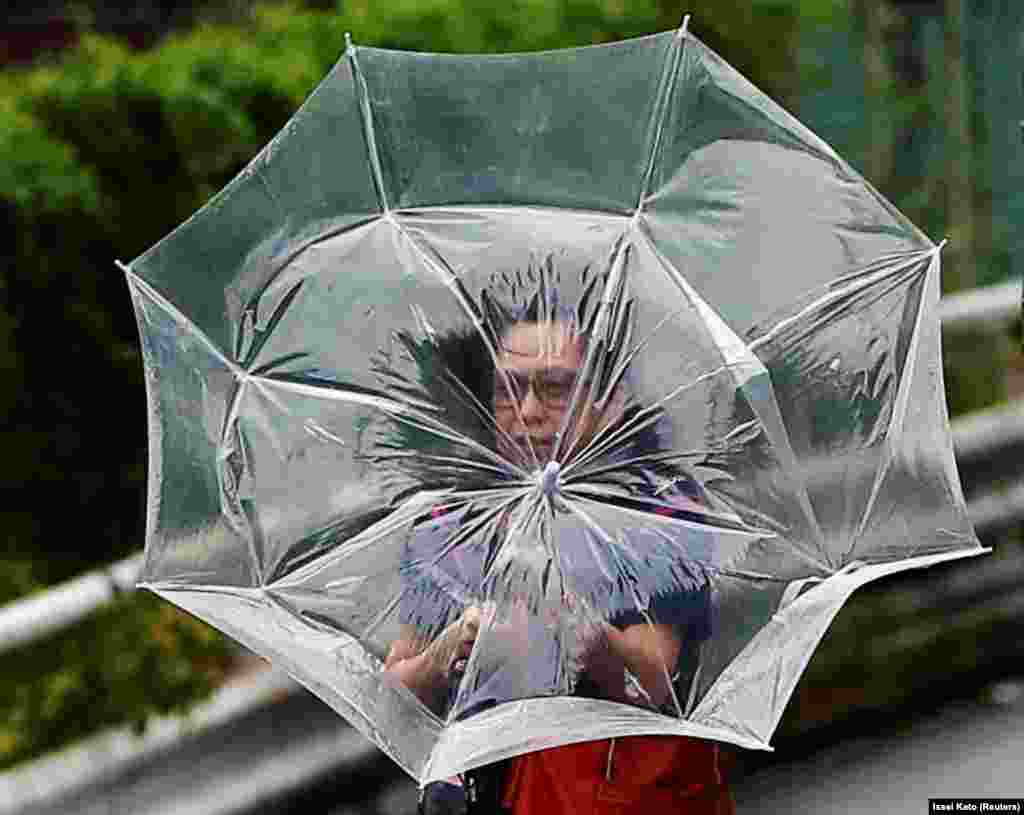 A woman using an umbrella struggles against heavy rain and wind caused by Typhoon Faxai in Tokyo, Japan. (Reuters/Issei Kato)